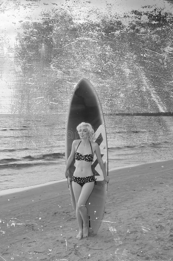 Pretty blond girl model like Marilyn Monroe with surfing board on a beach. Retro style, black and white stock images