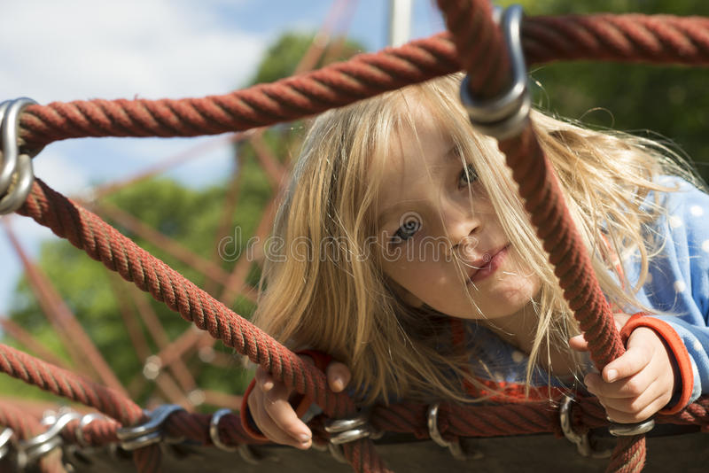 Pretty blond girl playing on rope of red web in summer royalty free stock image