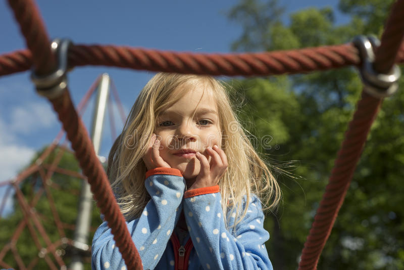 Pretty blond girl playing on rope of red web in summer stock photography