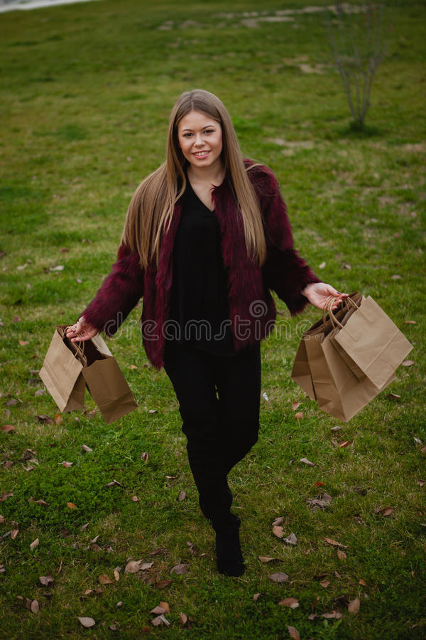 Pretty blond girl shopping. Pretty blond girl with fur coat shopping stock image