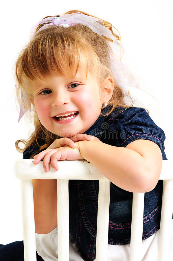 Pretty blond girl sitting on a chair royalty free stock photos