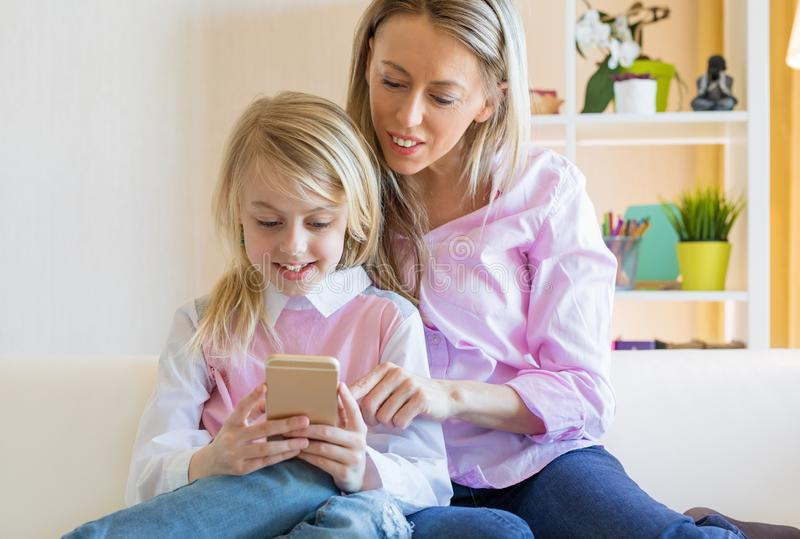 Pretty blond girl smiling and using mobile phone together with her mom stock images