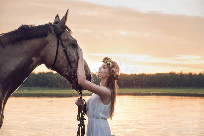 Pretty blond girl stroking a horse stock photo