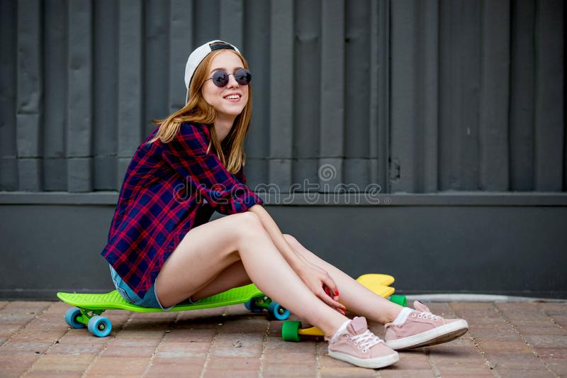 A pretty blond girl wearing sunglasses, checkered shirt and denim shorts is sitting on the bright logboards in front of royalty free stock photos