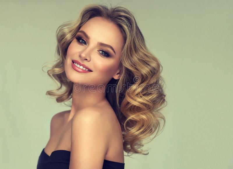 Pretty blond-haired model with curly, loose hairstyle and attractive makeup. stock photos