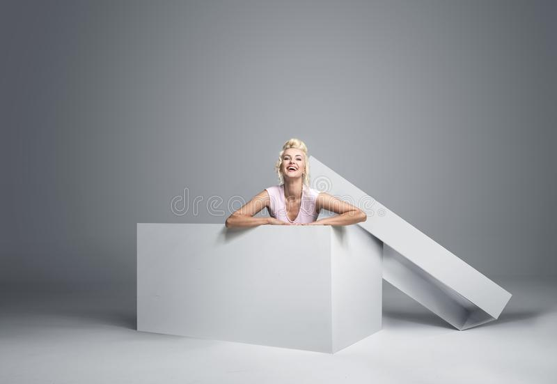 Pretty blonde getting off the gift box stock image