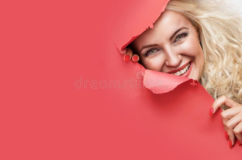 Pretty blond lady looking from behind of a red paper royalty free stock photography