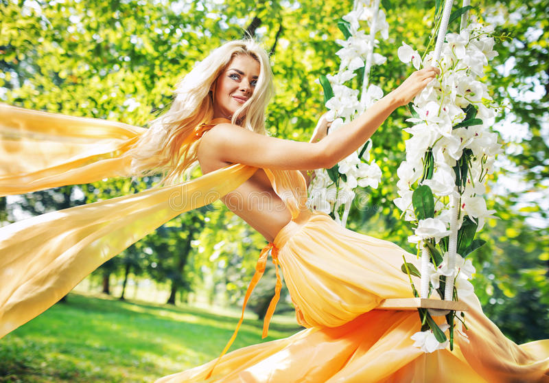 Pretty blond lady sitting on the ornate seesaw royalty free stock photography