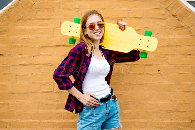 A pretty blond smiling girl wearing sunglasses, checkered shirt and denim shorts is standing in front of the brick wall royalty free stock photo