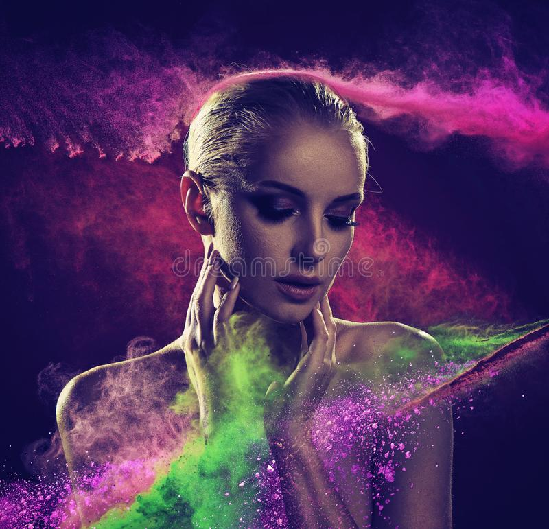 Pretty blond lady covered with colorful powder royalty free stock photos