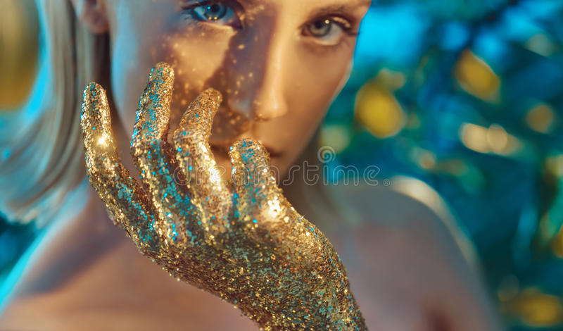 Pretty blond woman with golden, glittering hands stock photography