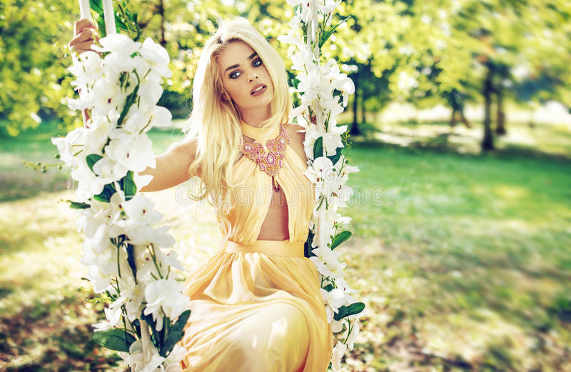 Pretty blond woman swinging on the ornate seesaw royalty free stock photo