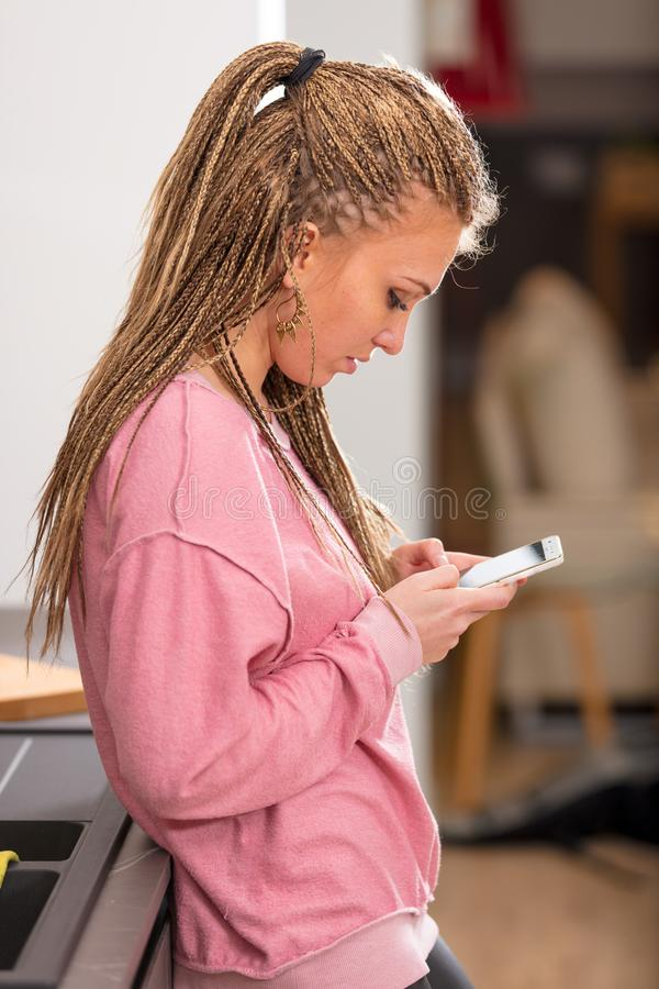 Pretty blond woman using her mobile indoors stock photo