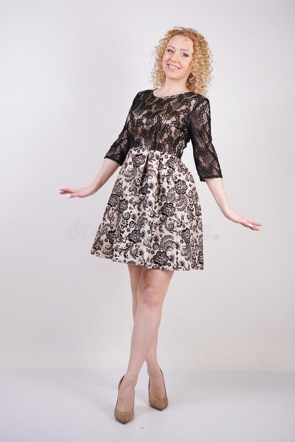 Pretty blonde adult woman wearing lace city dress and posing on white background isolated. fashion girl in the fashionable short e royalty free stock image