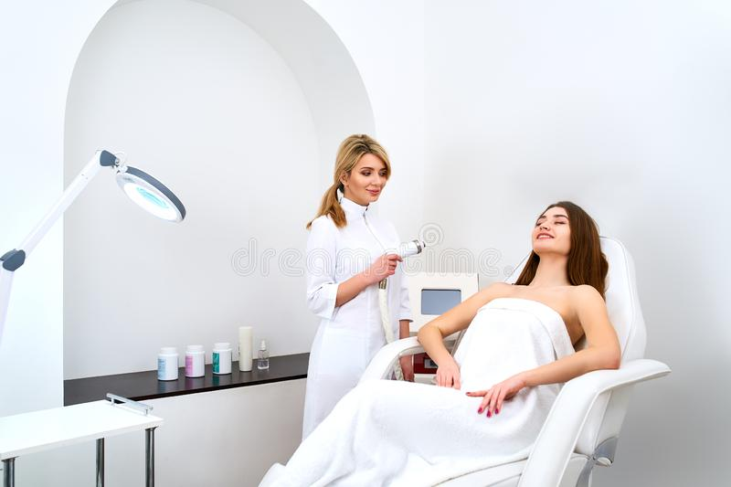 Pretty blonde beautician doctor doing rf-lifting procedure for woman laying in a beauty salon. Hardware cosmetology royalty free stock image