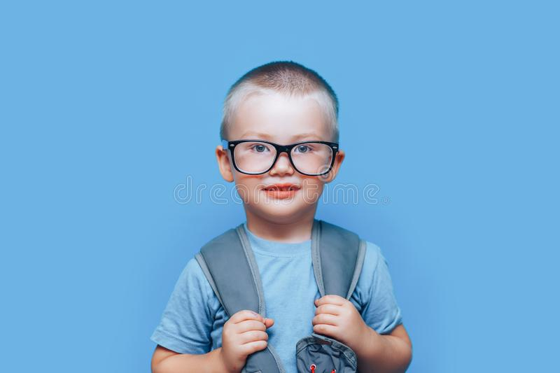 Pretty blonde boy on blue background with backpack unhappy, sad, child don`t want go to school. back to school royalty free stock photos