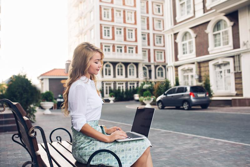 Pretty blonde business woman working on laptop on banch in city. She wears white shirt, blue skirt, looks busy. royalty free stock photography