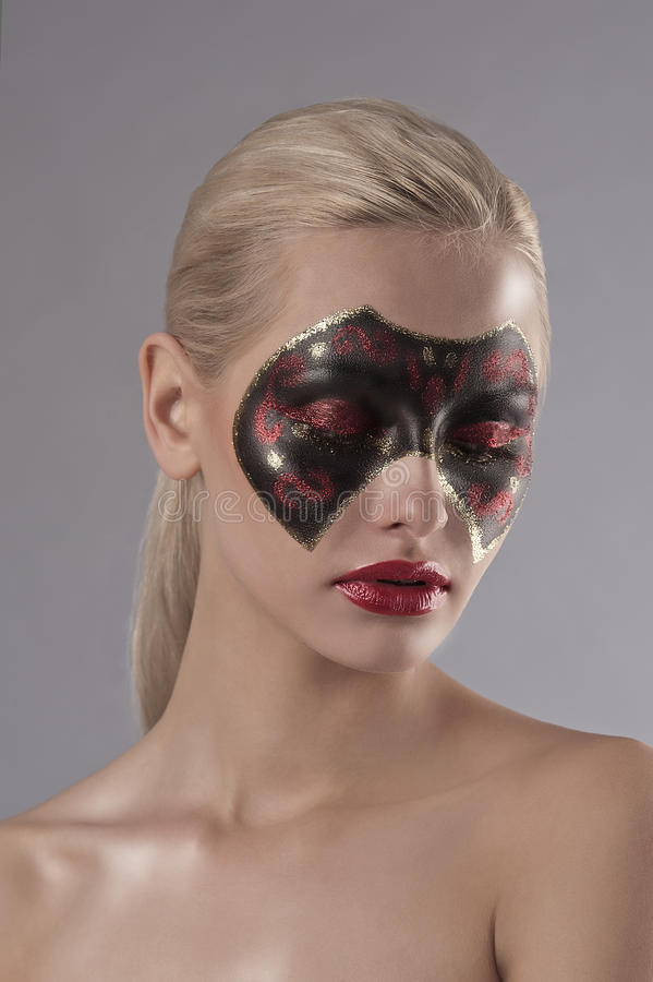 Pretty blonde with carnival mask painted on face stock photography