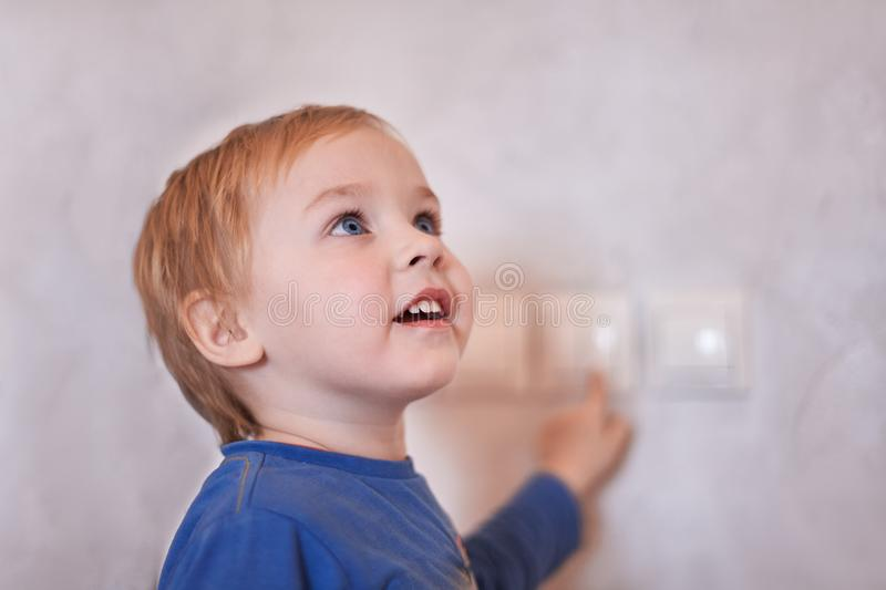Pretty blonde caucasian baby boy turns on/off the light-switch, looking up. Big blue eyes, close up portrait, copy space, indoors. Child at home royalty free stock images