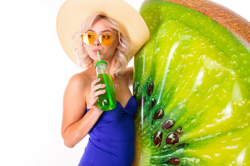 Pretty blonde caucasian female stands in swimsuit with rubber beach kiwi mattress, drink juice and smiles isolated on. White background stock images