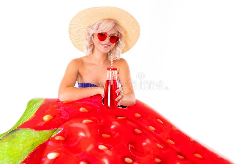Pretty blonde caucasian female stands in swimsuit with rubber beach strawberry mattress, juice and smiles isolated on royalty free stock photos