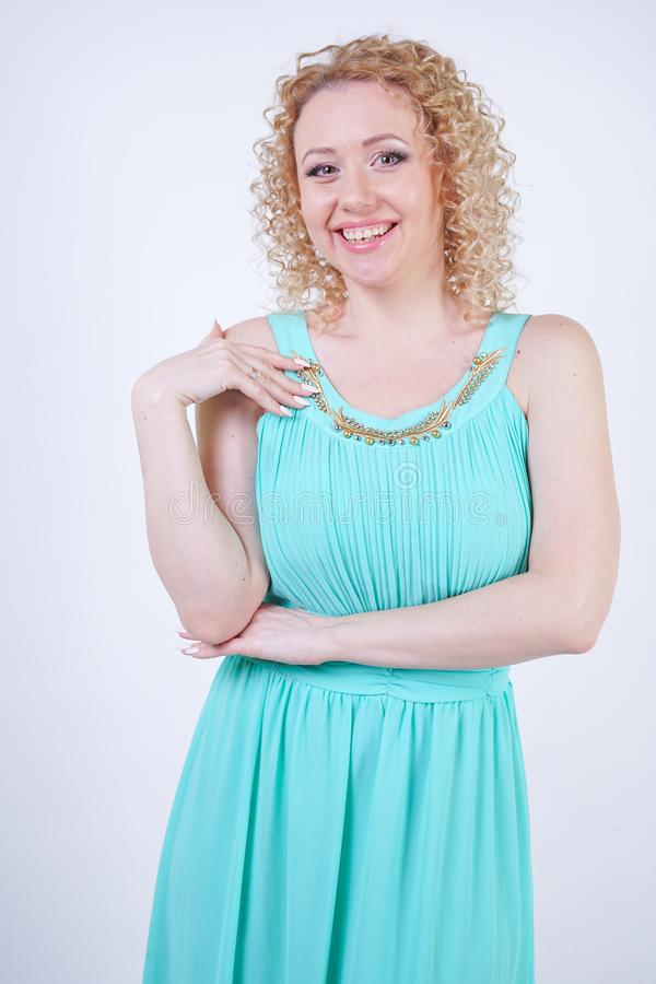 Pretty blonde caucasian woman wearing long blue fashion summer dress on white background stock photo