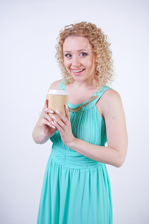 Pretty blonde caucasian woman wearing long blue summer dress holding paper cup of coffee and enjoys life on white studio backgroun royalty free stock image