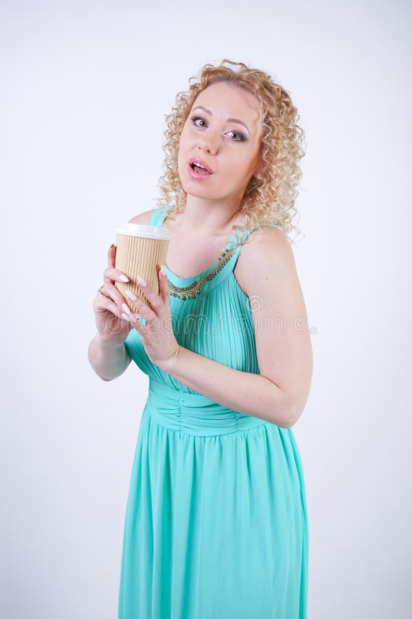 Pretty blonde caucasian woman wearing long blue summer dress holding paper cup of coffee and enjoys life on white studio backgroun royalty free stock photography