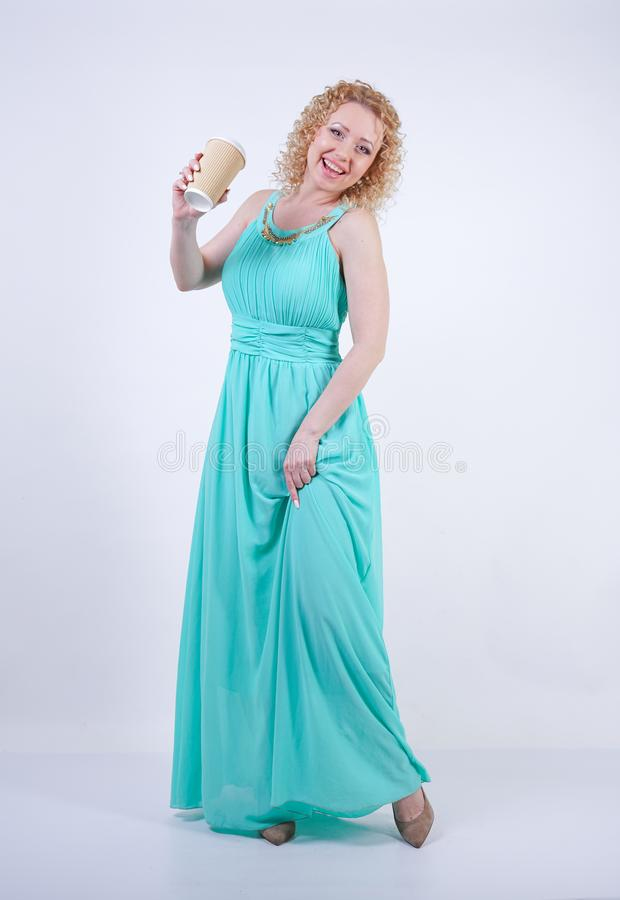 Pretty blonde caucasian woman wearing long blue summer dress holding paper cup of coffee and enjoys life on white studio backgroun royalty free stock photo
