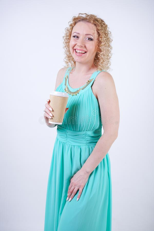 Pretty blonde caucasian woman wearing long blue summer dress holding paper cup of coffee and enjoys life on white studio backgroun stock image