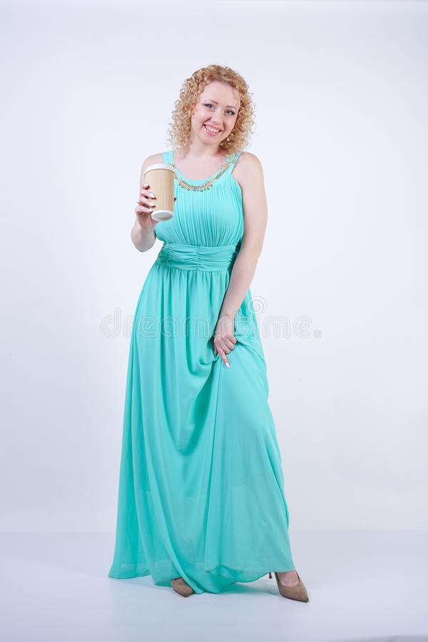 Pretty blonde caucasian woman wearing long blue summer dress holding paper cup of coffee and enjoys life on white studio backgroun stock images