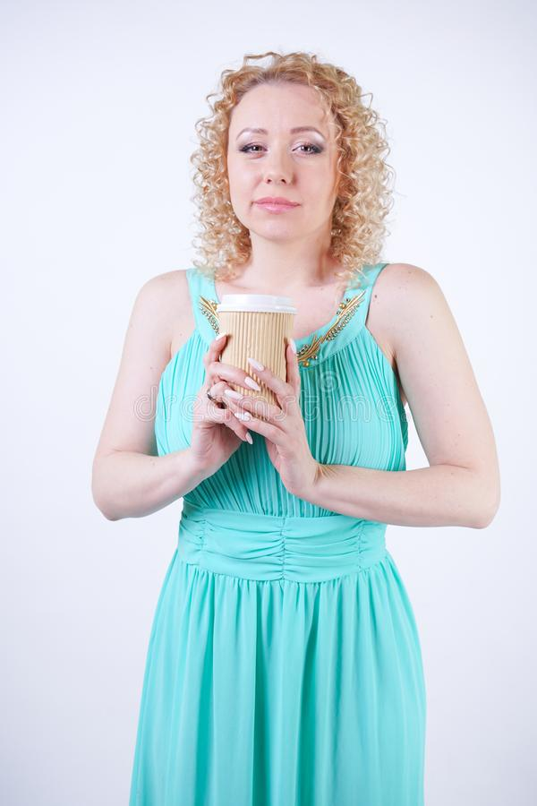 Pretty blonde caucasian woman wearing long blue summer dress holding paper cup of coffee and enjoys life on white studio backgroun royalty free stock photos