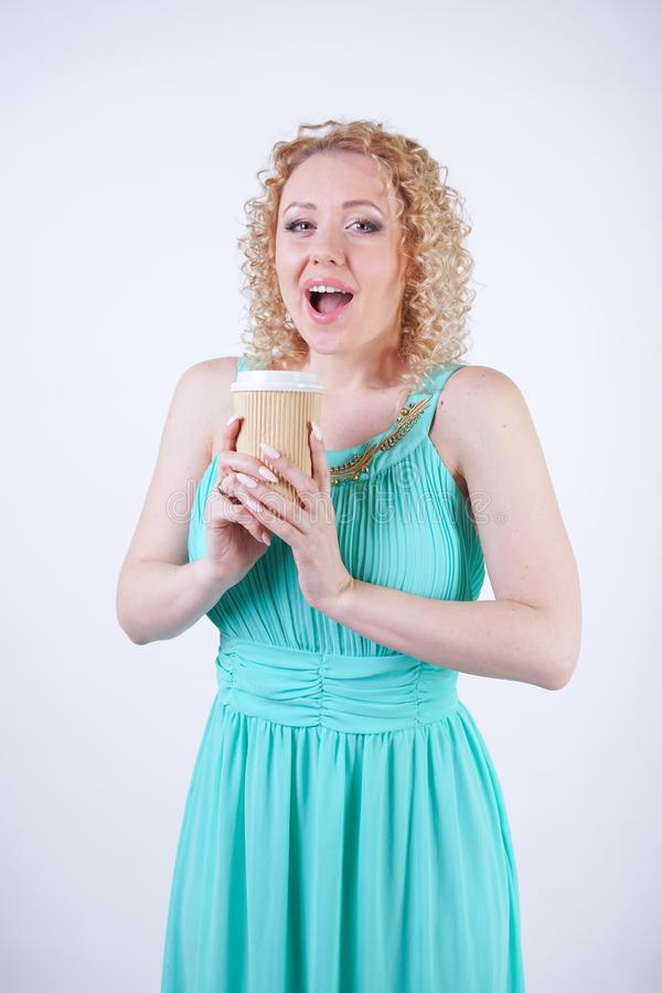 Pretty blonde caucasian woman wearing long blue summer dress holding paper cup of coffee and enjoys life on white studio backgroun royalty free stock images