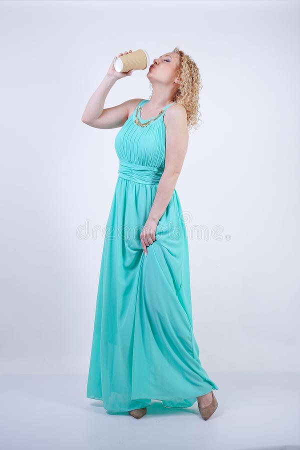 Pretty blonde caucasian woman wearing long blue summer dress holding paper cup of coffee and enjoys life on white studio backgroun stock photo
