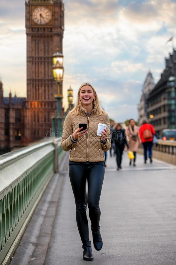A pretty city woman with a coffee and a mobile phone in her hands walks down Westminster Bridge in London, UK royalty free stock image