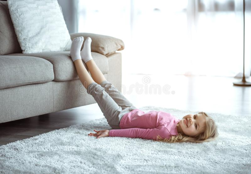 Pretty blonde female kid resting on flooring near couch royalty free stock image