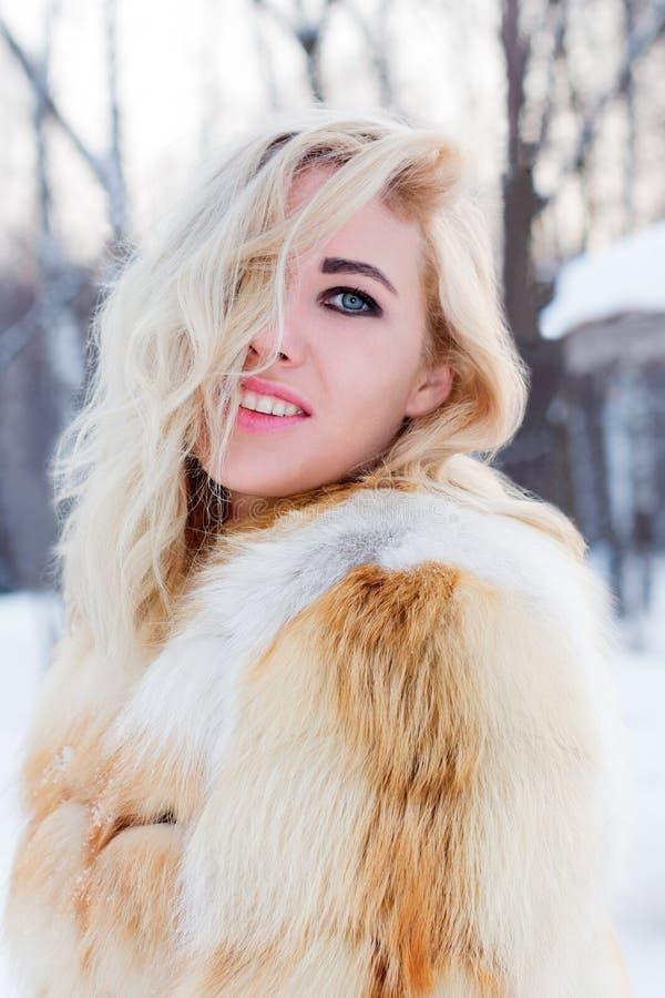 Pretty blonde in fur coat smiles in winter day in park royalty free stock image