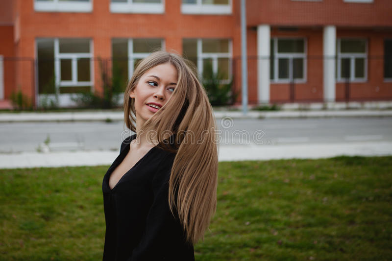 Pretty blonde girl with a beautiful long. An grass of background stock photography