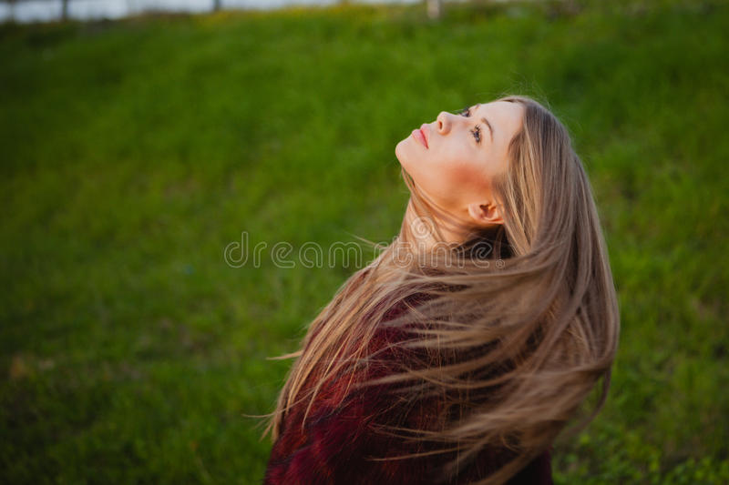 Pretty blonde girl with a beautiful long. An grass of background stock photos