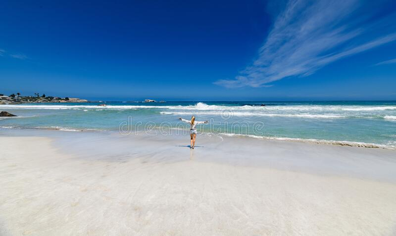 A pretty blonde girl on the beautiful white sand beaches of clifton in the capetown area of south africa. A pretty blonde girl walking down to the sea on the stock images
