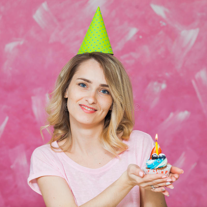 Pretty blonde girl in birthday cap hold cupcake with candle royalty free stock image