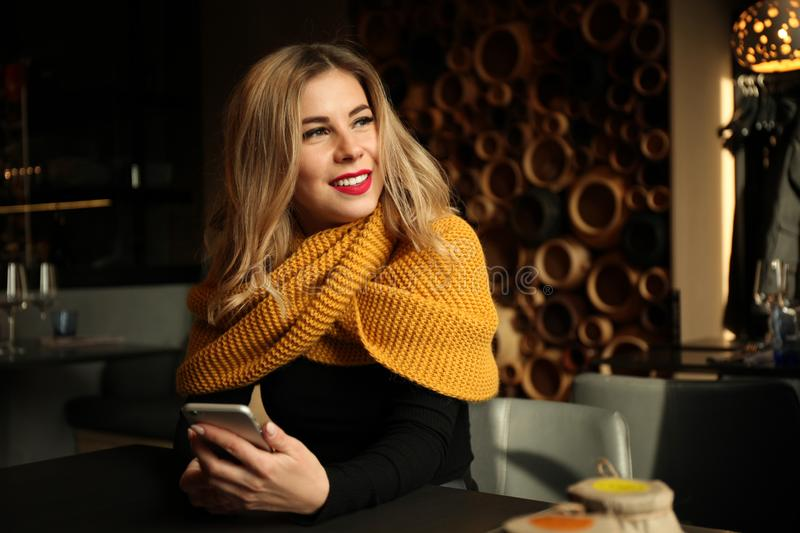 Pretty blonde girl in cafe uses smartphone and smiling royalty free stock photos