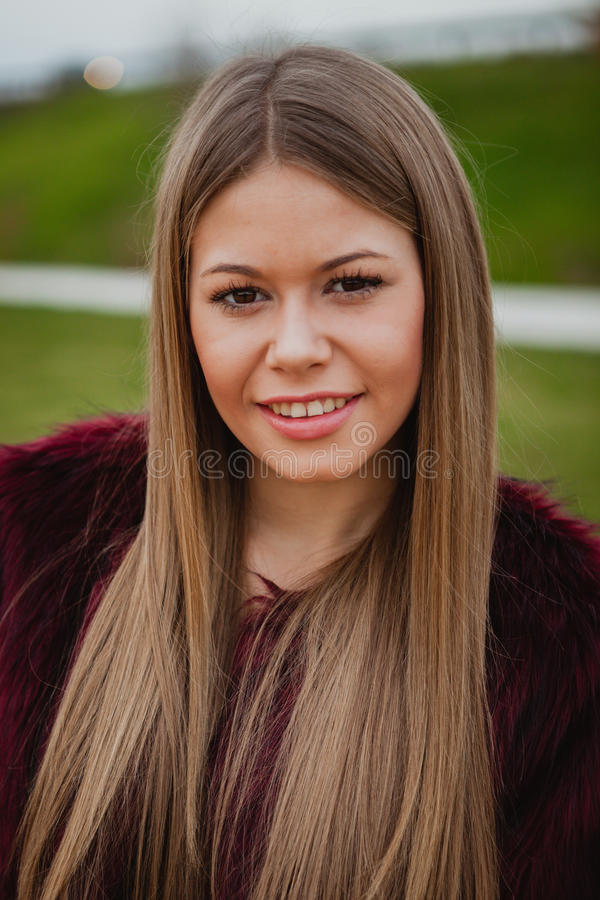 Pretty blonde girl with fur coat. In the park at winter royalty free stock photography