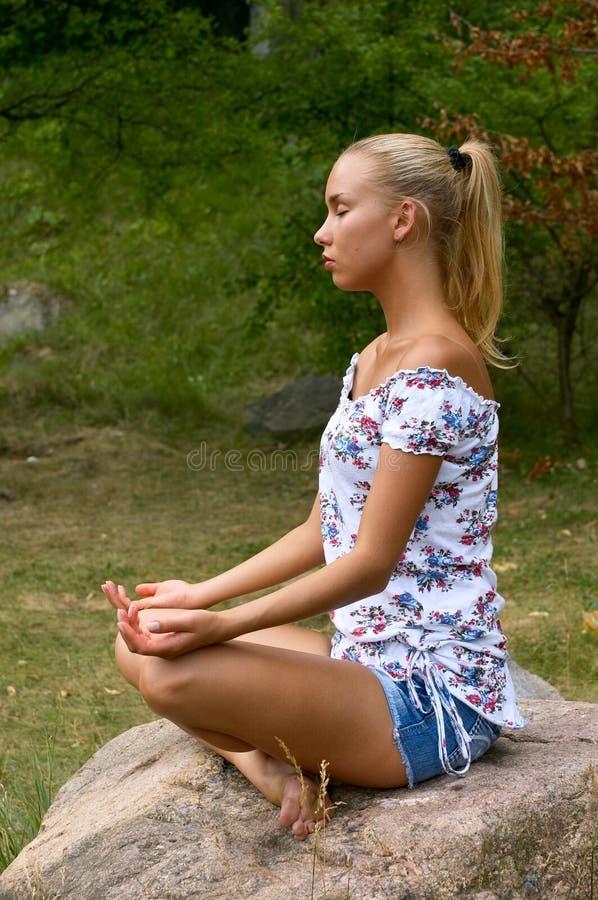 Pretty blonde girl meditating royalty free stock photography