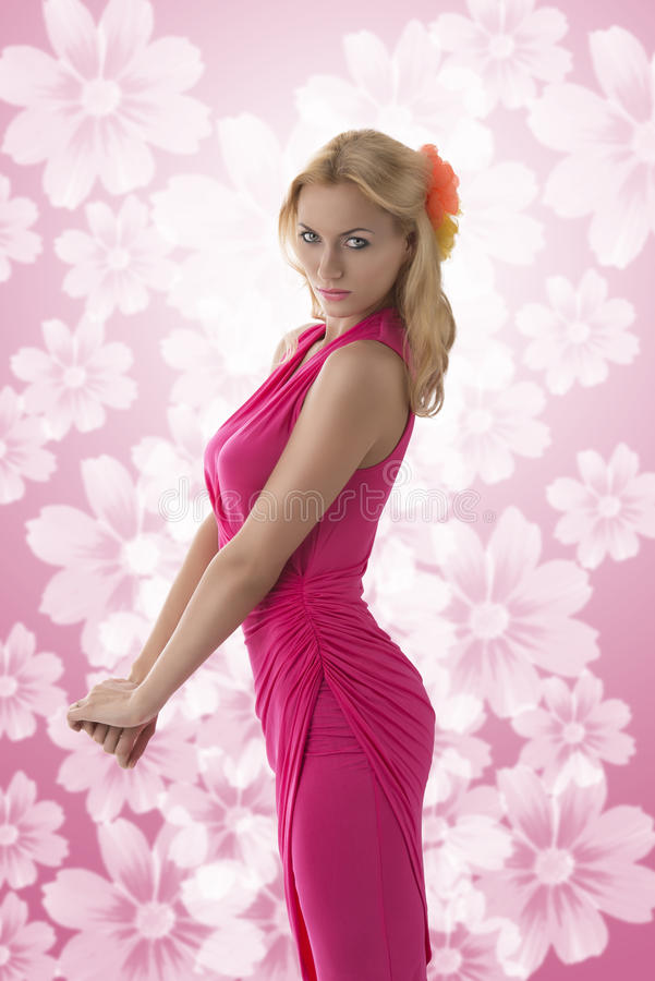 Pretty blonde girl with pink dress in profile stock photos