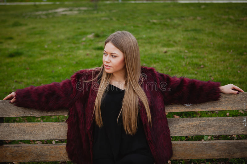 Pretty blonde girl sittig in a bench in the park royalty free stock photos