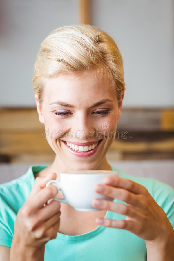 Pretty blonde holding cup of coffee. At the cafe royalty free stock photography