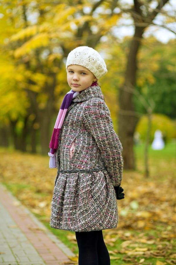 Pretty blonde little girl in jacket looking back stock image