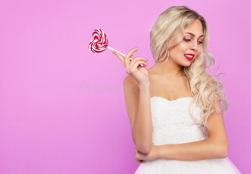 Pretty blonde with a lollipop. Thoughtful blonde. Beautiful blonde on pink background. royalty free stock image