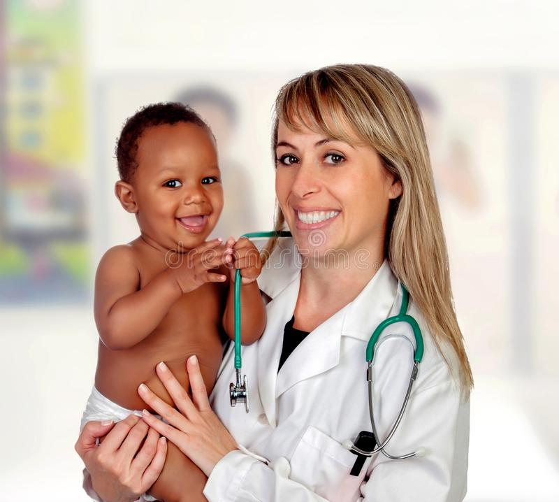 Pretty blonde pediatrician with a beautiful African American baby in arms stock images